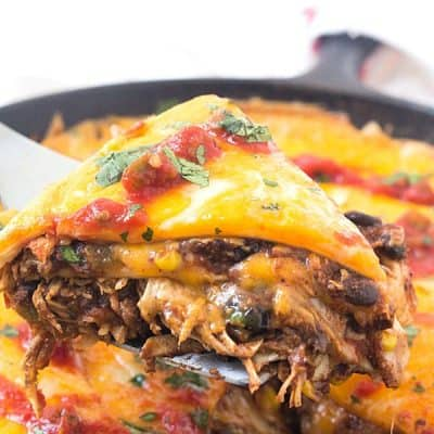 Mexican Skillet Pie - Also known as a Mexican skillet casserole. Layered with tortillas, enchilada sauce with black beans and corn, and taco-seasoned shredded chicken! Our family also likes to call it a Mexican skillet dinner - we always seem to have it for dinner and makes quite a bit! Perfect dish to add to your Cinco de Mayo recipes!