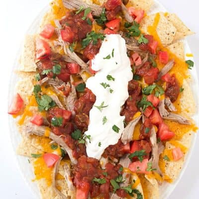 Pulled Pork Nachos - Fall off the bone pulled pork on top of tortillas with shredded cheese, then loaded with diced tomatoes, salsa, sour cream, and cilantro!