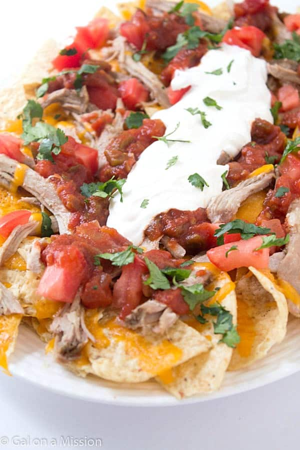 Pulled Pork Nachos - Fall off the bone pulled pork cooked in the slow cooker then loaded with your favorite toppings! Consider them nachos supreme!