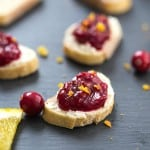 Cranberry Orange Crostini - A decadent crostini made with an out-of-this-world cheese spread, then topped with fresh cranberry sauce and orange zest! Perfect appetizer for the holidays.