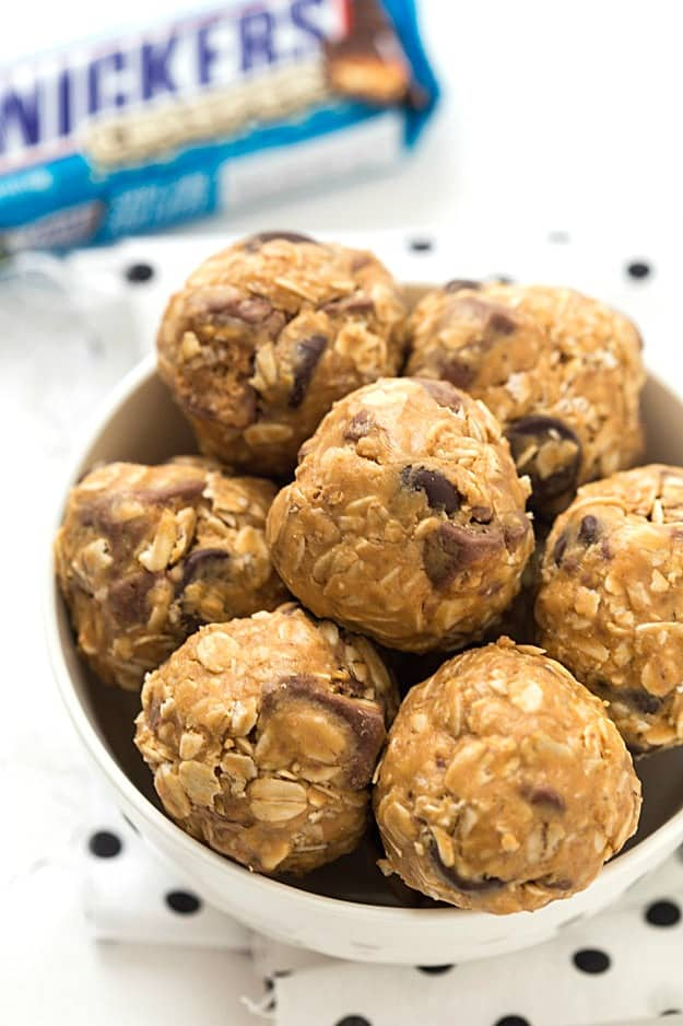 No-Bake Snickers Granola Bites Recipe - So much easier than granola bars! The perfect healthier snack or on-the-go treat made with old-fashioned oats, peanut butter, and honey as the base. Made without flour and white sugar!