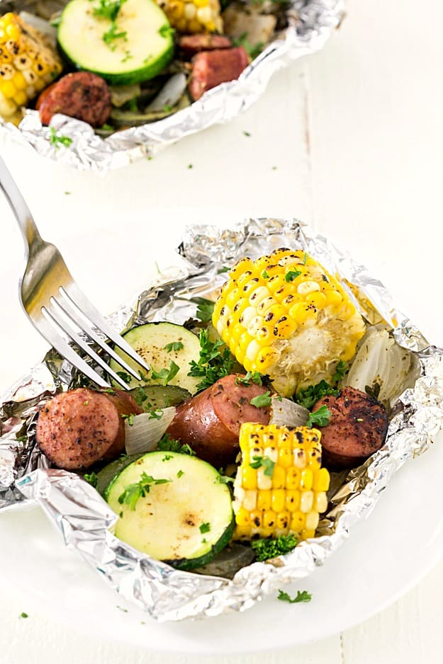 Kielbasa Sausage & Grilled Vegetables in Foil - These foil packets are so quick to assemble! Perfect for camping or a quick dinner. Packed with sausage, zucchini, and corn with the most amazing seasoning! A family favorite any night of the week.