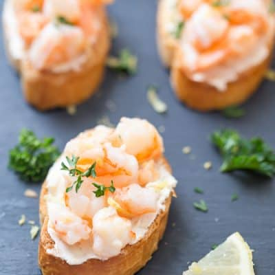 Shrimp Scampi Crostini - This shrimp scampi crostini is the perfect addition to your holiday party menu or even for game day! It's simple, it's elegant, and it has the perfect butter, lemon, garlic ratio! Impress your guests with incredibly flavorful and easy crostini.