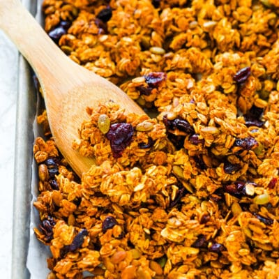 Homemade pumpkin granola on a baking sheet with a wooden spoon