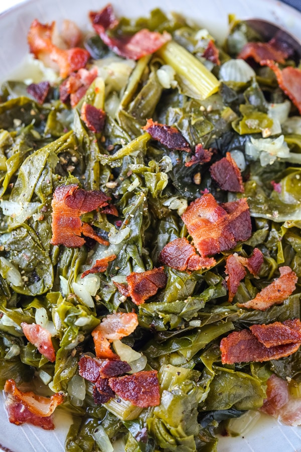 Looking down on a small plate of cooked collar greens with bacon