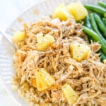 Small plate containing shredded chicken with a homemade teriyaki sauce over the top with pineapple chunks and green beans on the side