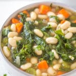 looking down on a bowl of soup with white beans, carrots, and kale