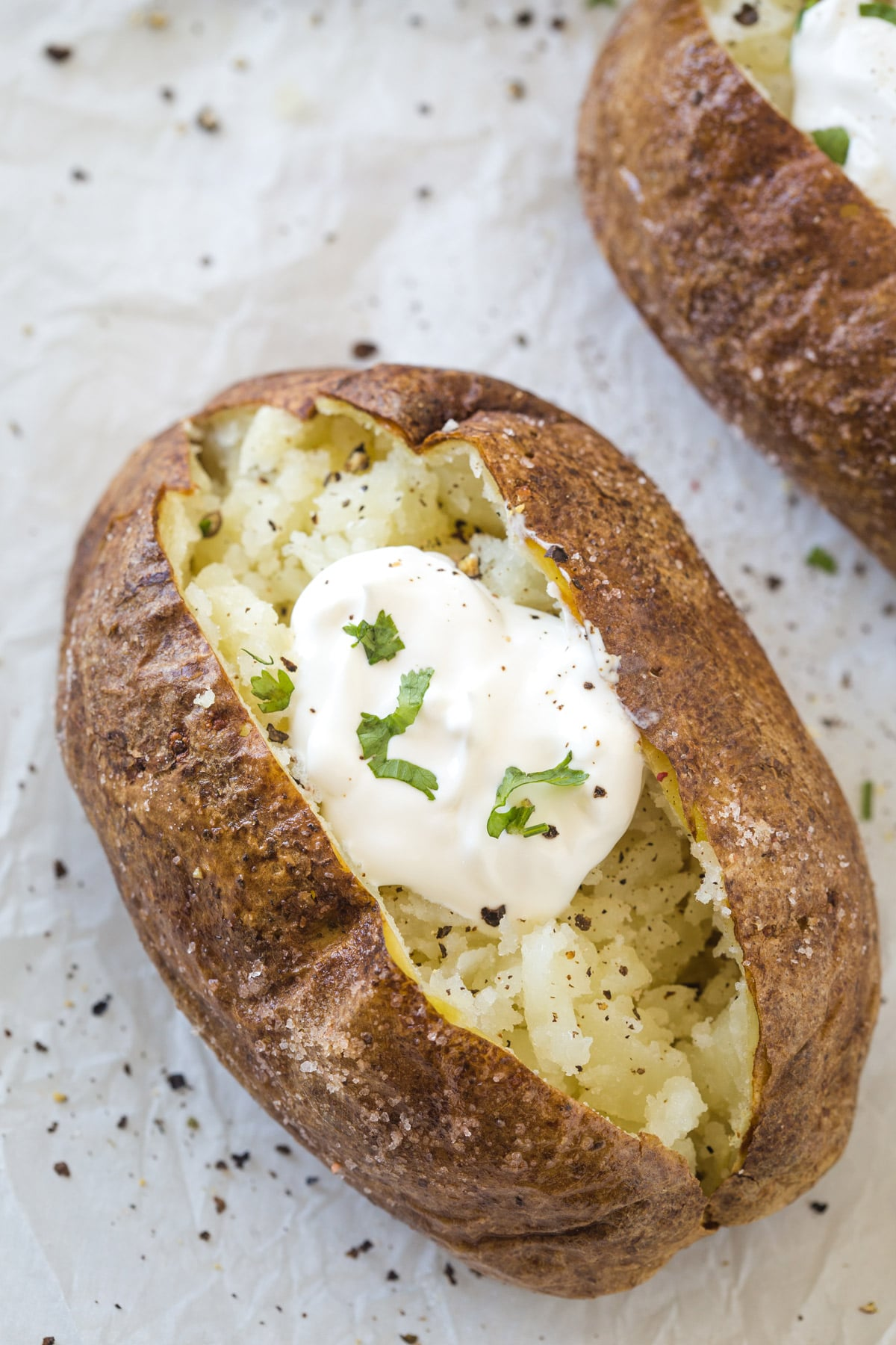 Looking down on a cooked baked potato topped with sour cream, salt, pepper, and parsley