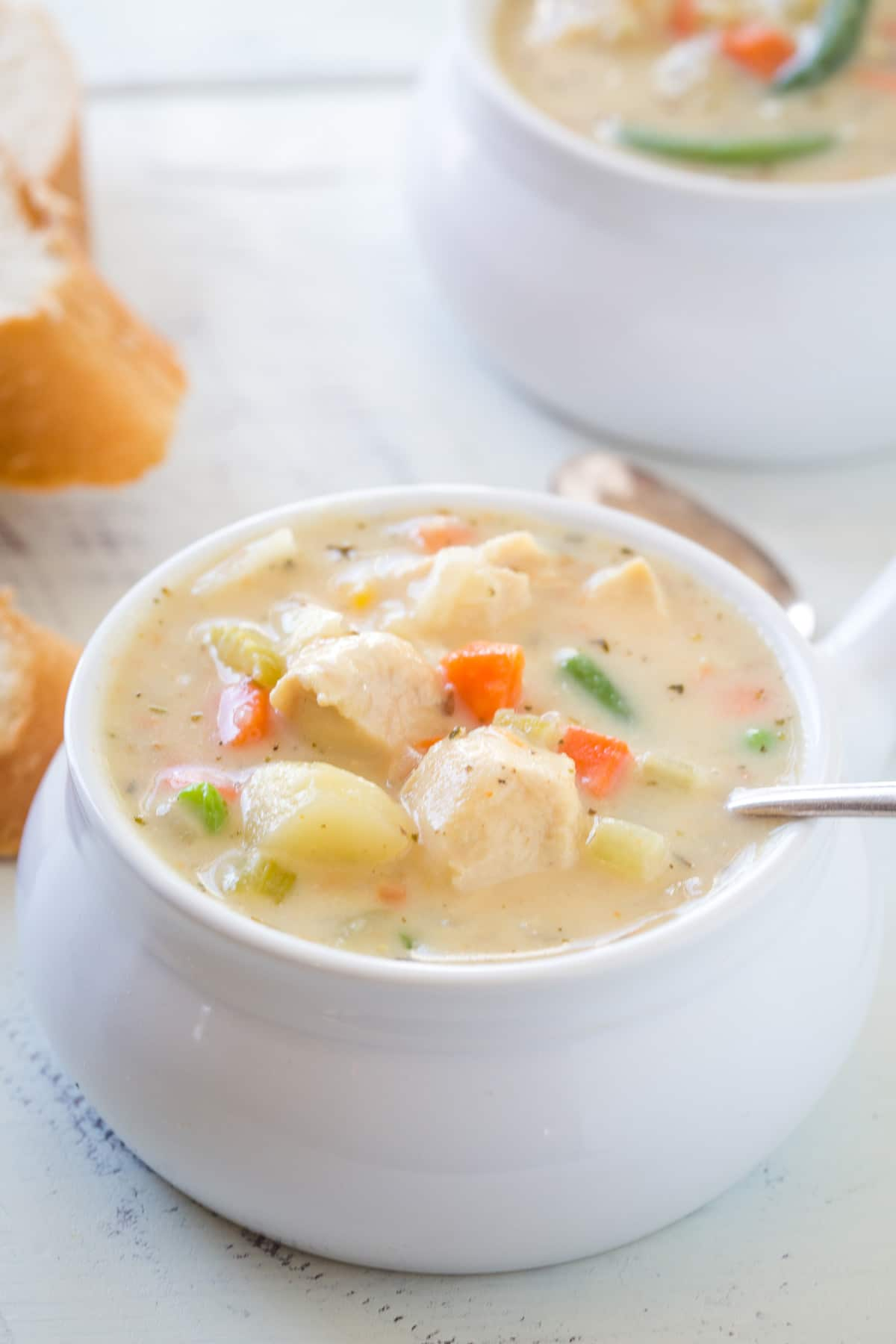 Looking at chicken pot pie soup is a soup bowl with a spoon