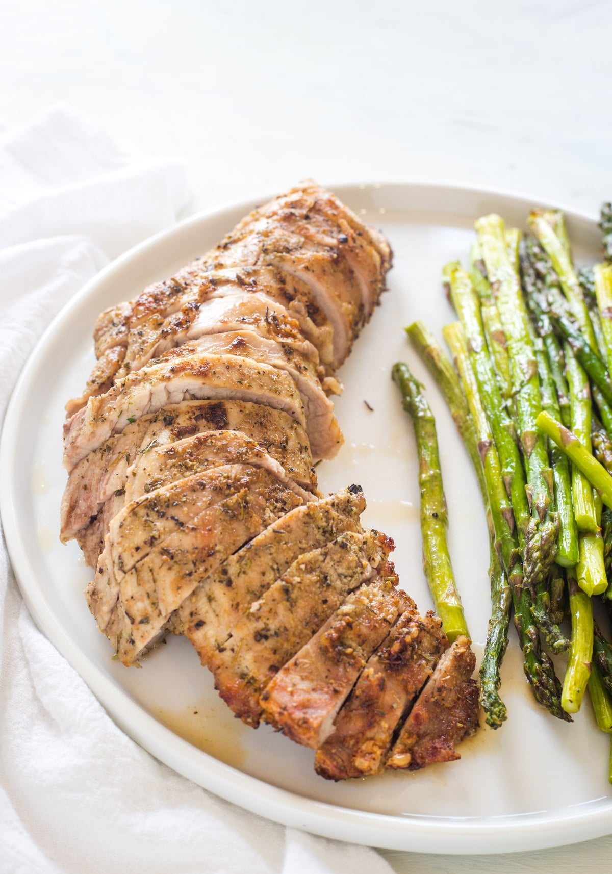 Looking at a cooked and sliced pork tenderloin on a white plate with asparagus
