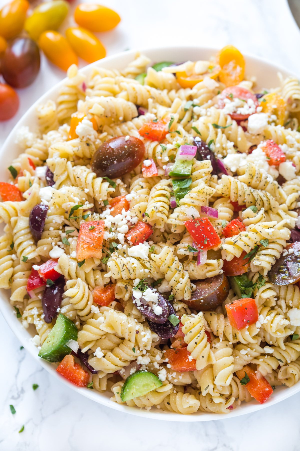 Close up of Greek pasta salad in a bowl bowl on a marble surface