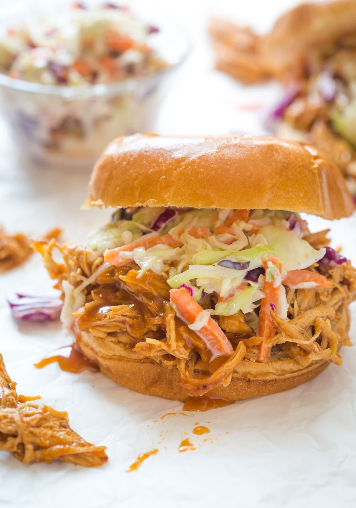 shredded bbq chicken with bbq sauce on top of a bun with coleslaw